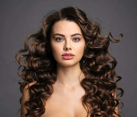 Hermosa mujer joven con cabello castaño largo y rizado y maquillaje de ojos ahumado. Chica morena sexy y hermosa con un peinado ondulado. Retrato de una mujer atractiva. Modelo. Foto de archivo