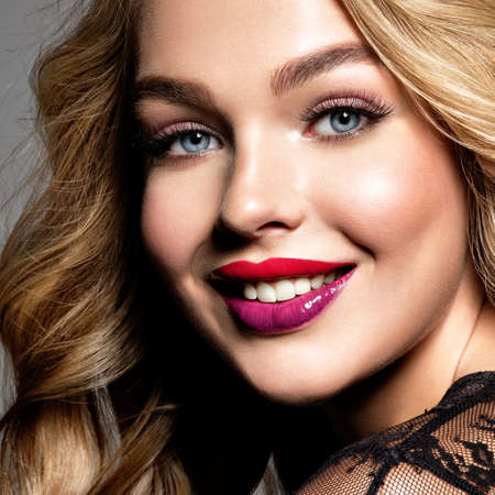 Blond smiling woman with long curly beautiful hair. Makeup. Fashion make-up. Fashionable girl dressed in black dress. Closeup portrait. Gorgeous face of an attractive fashion model. Bright red lips. P