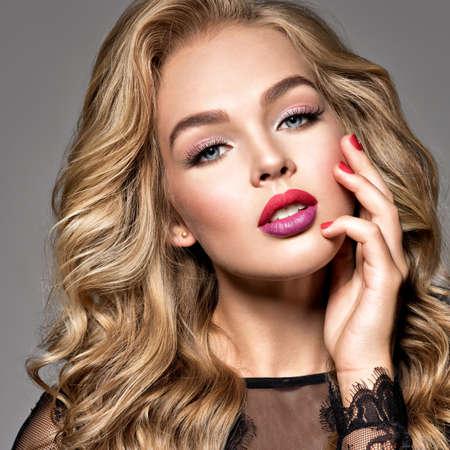 Femme blonde aux beaux cheveux longs et bouclés. Se réconcilier. Maquillage de mode. Fille à la mode vêtue d'une robe noire. Portrait en gros plan. Visage magnifique d'un mannequin attrayant. Lèvres rouge vif.
