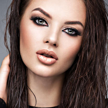 Beauty face of the young beautiful woman. Gorgeous female portrait with slicked brown hair. Young adult girl with healthy skin. Pretty model with fashion smokey eye makeup. Skin care concept. Professi