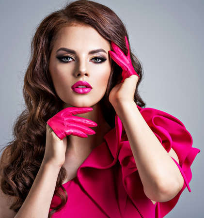 Fashionable woman in a red dress with a creative eye makeup. Closeup portrait of a beautiful stylish girl wearing pink gloves. Sexy young woman with beautiful face with red lipstick.