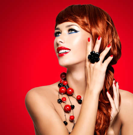 Beautiful fashionable woman with red nails and red hairs. Portrait of a fashion model with bright eye makeup 写真素材