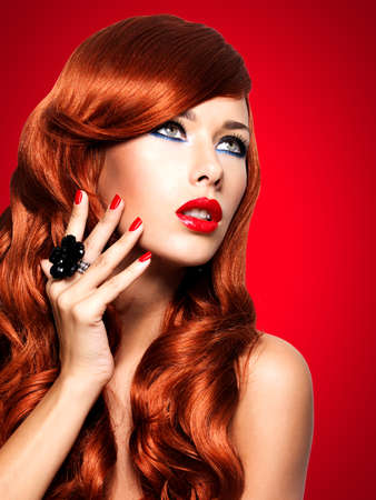 Beautiful sensual woman with long red hairs and red nails -  isolated on white. 写真素材 - 122593770