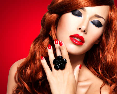 Beautiful fashionable woman with red nails and red hairs. Portrait of a fashion model with bright eye makeup -   isolated on white.