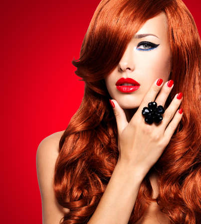 Beautiful woman with long red hairs with sexy bright lips and red nails.  Portrait of a fashion model with covered face by hairs