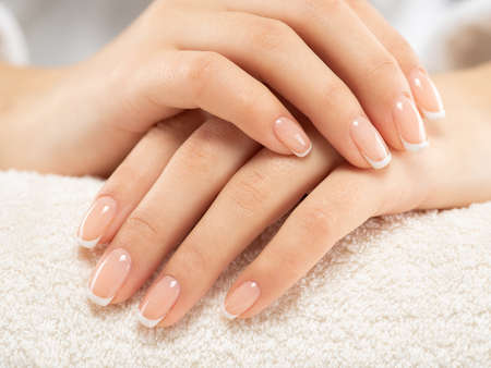 Woman gets manicure procedure in a spa salon. Beautiful female hands. Hand care. Woman cares for the nails on hands. Beauty treatment with skin of hand.   Woman's hands close-up view. 写真素材 - 122595848