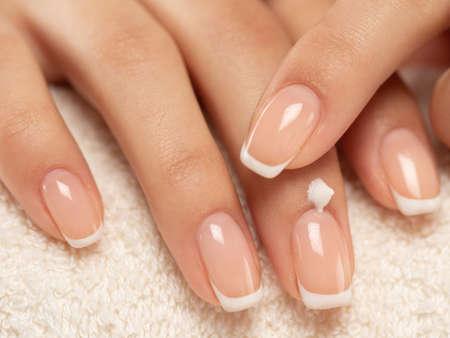 Frau trägt eine kosmetische Feuchtigkeitscreme auf ihre Hände auf. Schöne weibliche Hände. Frau bekommt Maniküre-Verfahren in einem Spa-Salon. Handpflege. Frau kümmert sich um die Hände. Schönheitsbehandlung mit Haut der Hand.