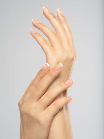 Kobieta dostaje zabieg manicure w salonie spa. Piękne kobiece dłonie. Pielęgnacja dłoni. Kobieta dba o paznokcie na dłoniach. Zabieg pielęgnacyjny na skórę dłoni. Widok z bliska ręce kobiety. Zdjęcie Seryjne