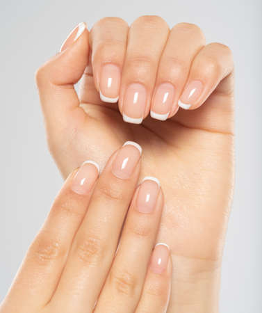 Beautiful female hands. Woman hands with beautiful french manicure, nails.  Hand care. Woman cares for the nails on hands. Beauty treatment with skin of hand.   Womans hands close-up view. 写真素材