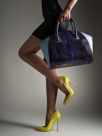 Beautiful woman with a slim legs in yellow high heels. Fashionable girl holds stylish blue bag. Glamour stylish concept. Art. Woman walks after shopping. Unrecognizable female. 写真素材