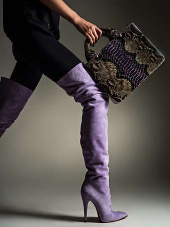 Beautiful woman in purple high boots. Fashionable girl holds stylish violet leather bag. Glamour stylish concept. Art. Model walks after shopping. 写真素材 - 122676998