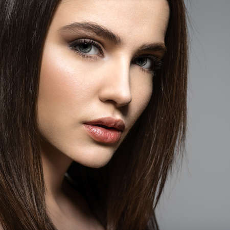 Closeup face of a Fashion model with straight   hair.  Fashion model posing at studio. Pretty woman with long straight brown hair looking at camera.