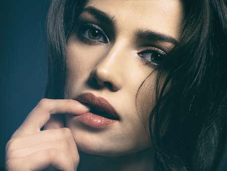 Bella donna con capelli castani. Modello attraente con occhi marroni. Modella con un trucco fumoso. Il ritratto del primo piano di una donna graziosa esamina la macchina fotografica.