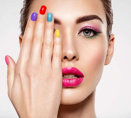 Schöne Modefrau mit farbigen Nägeln. Attraktives weißes Mädchen mit Mehrfarbenmaniküre. Glamour-Mode-Modell mit hellem Glanz-Make-up posiert im Studio. Stilvolles modisches Konzept. Kunst