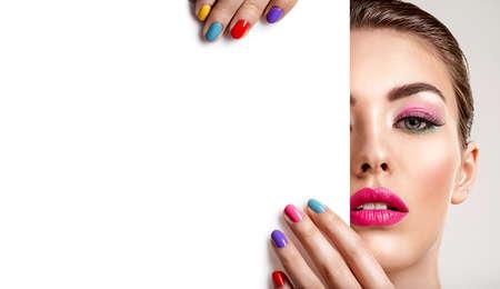 Mooie vrouw met een gekleurde manicure houdt lege poster. Aantrekkelijk wit meisje met leeg reclamebord. Glamour fashion model houdt plakkaat, vrije ruimte. Modieus advertentieconcept. Kunst