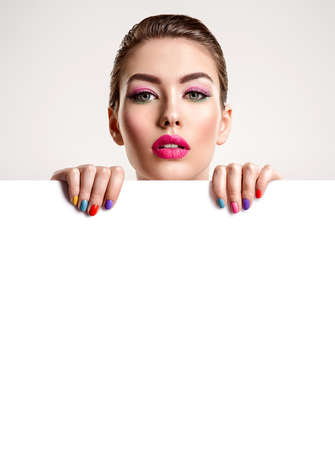 Beautiful  woman with a colored manicure holds blank poster. Attractive white girl with empty billboard. Glamour fashion models holding placard, free space. Fashionable  advertisment concept. Art