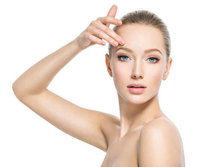 Beautiful face of young caucasian woman with perfect health skin  - isolated on white.  Skin care concept. Female Model touches face. 写真素材 - 122677534