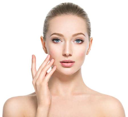 Piękna twarz młodej kobiety rasy kaukaskiej z idealną skórą zdrowia - na białym tle. Koncepcja pielęgnacji skóry. Modelka dotyka twarzy.