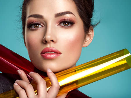Beautiful fashion woman with  a colored  items.  Attractive white girl with living coral lipstick. Glamour fashion model with bright gloss make-up posing at studio. Stylish fashionable concept. Art. F