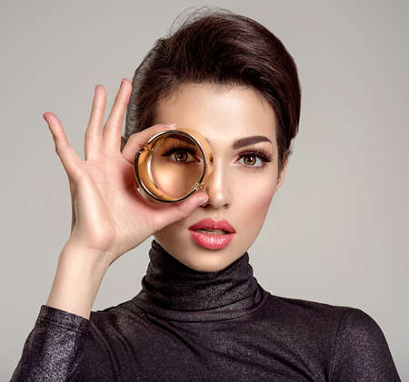 Beautiful young woman looks through bracelet. Eyesight. Vision. Gaze. Attractive white girl wears luxury jewelry.  Glamour fashion model with bright  make-up. Stylish fashionable concept.