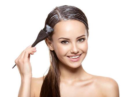 Femme souriante coloration des cheveux avec une brosse sur fond blanc