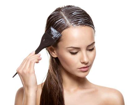 Jeune femme coloration des cheveux avec une brosse sur fond blanc