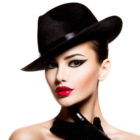 Ð¡lose-up portrait of a woman in a black hat and gloves with red lips posit at studio