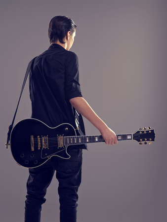 Fifteen years old guitarist with a  black electric guitar. Teenage musician holds guitar, posing at studio. The young caucasian guy with a guitar. Stylish musician. Heavy metal player, rear view. Banque d'images - 129141017