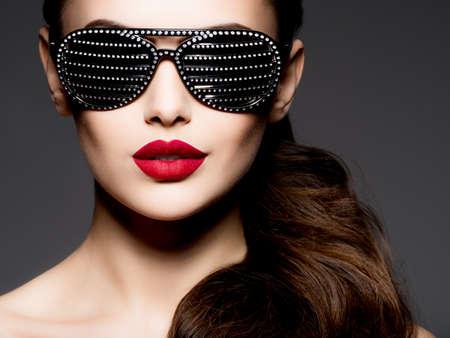 Retrato de moda de mujer con gafas de sol negras con diamantes y labios rojos