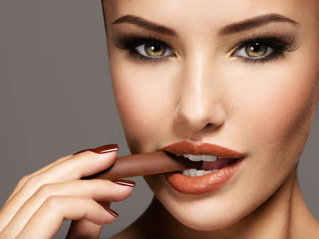 Portrait of glamour beautiful woman holds and eats  chocolate candy. Photo in brown color style