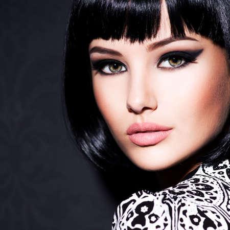 Clouseup-Porträt der schönen Frau mit hellem Glamour-Make-up und kurzen schwarzen glatten Haaren, die im Studio posieren.