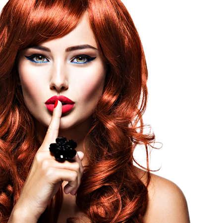 Hermosa mujer con pelos rojos, dedo en los labios. Secreto. Moda