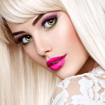 Portrait of a Beautiful woman with pink make-up and long white straight hairs. Face of a Fashion model with pink lipstick. Pretty girl posing at studio. Stock Photo