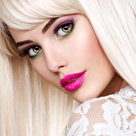Retrato de una mujer hermosa con maquillaje rosa y largos cabellos rectos blancos. Rostro de un modelo de moda con lápiz labial rosa. Chica guapa posando en el estudio. Foto de archivo