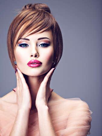 Schönes Rothaarigemädchen mit Stilfrisur. Porträt einer jungen Frau mit großen blauen Augen. Model posiert im Studio.