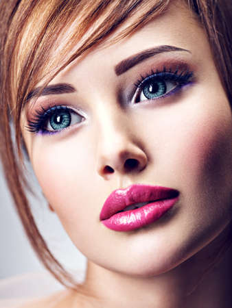 Attractive young woman with beautiful big blue eyes. Closeup face of an amazing girl with lips. Imagens