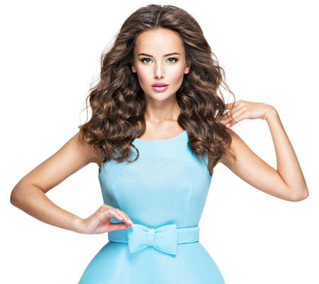 Beautiful fashionable woman with long hair in blue dress. Attractive fashion model posing on white background. Фото со стока