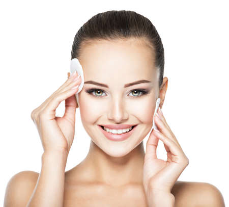 Beautiful woman cleans the face with cosmetic cotton swab. Reklamní fotografie