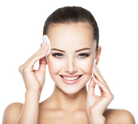 Bella mujer limpia la cara con hisopo de algodón cosmético. Foto de archivo