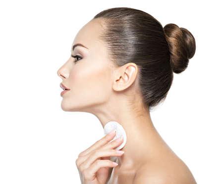 Bella donna pulisce il collo con un batuffolo di cotone cosmetico.