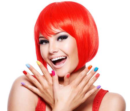 Fronte del primo piano di una ragazza espressiva divertente con unghie multicolori luminose. Modella in posa su sfondo bianco Archivio Fotografico