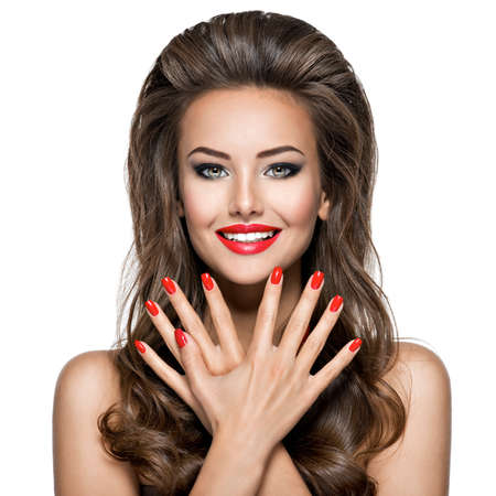Portrait of beautiful smiling young woman with red nails and lips on white background.