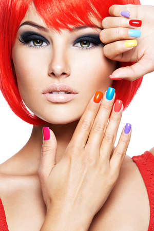 Close-up face of a beautiful girl with brown eye makeup and bright multicolor nails. Fashion model posing on white background Imagens