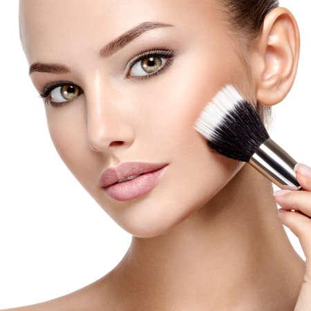 Portret van een vrouw die cosmetische make-up op het gezicht aanbrengt met behulp van een make-upborstel. Stockfoto
