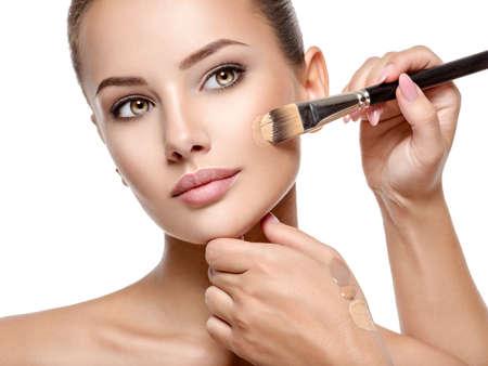 Artista de maquillaje aplicando base tonal líquida en el rostro de la mujer