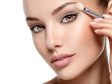 Beautiful woman applying eyeshadow use makeup brush