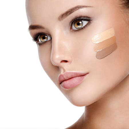 Beau visage de jeune femme avec fond de teint cosmétique sur une peau. Concept de traitement de beauté