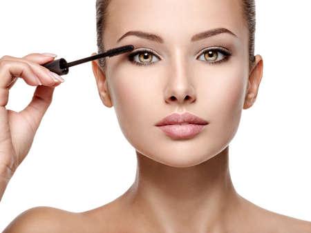 Femme appliquant du mascara cosmétique sur les cils à l'aide d'une brosse à friser - isolated on white