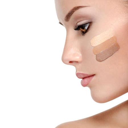Schönes Gesicht der jungen Frau mit kosmetischer Grundlage auf einer Haut. Beauty-Behandlungskonzept