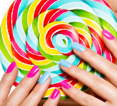 female fingers with colorful nails on the background of vivid multicolor sweet candy